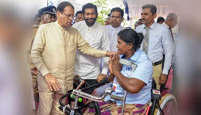 President presents a tricycle of Development Lotteries Board to female Sales Assistant