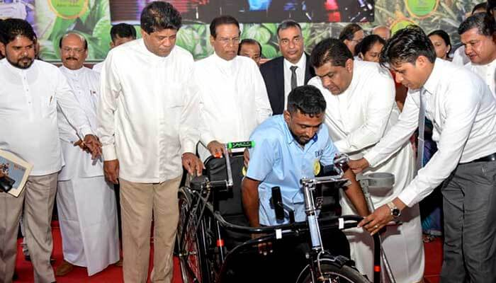 H.E. the President presents a tricycle to a Sales Assistant of DLB